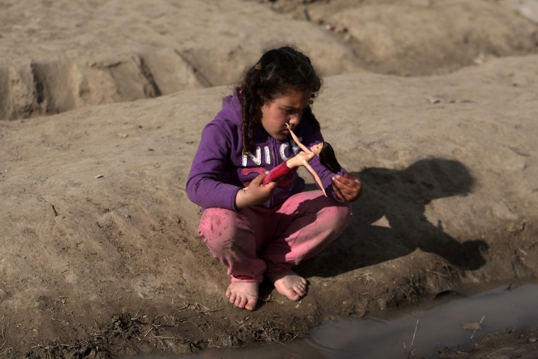 Image: A migrant girl plays with her doll at the makeshift camp at the Greek-Macedonian border