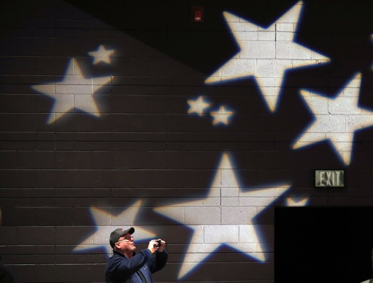 Image: An attendee takes a photograph at a campaign event for U.S. Republican presidential candidate Donald Trump in De Pere