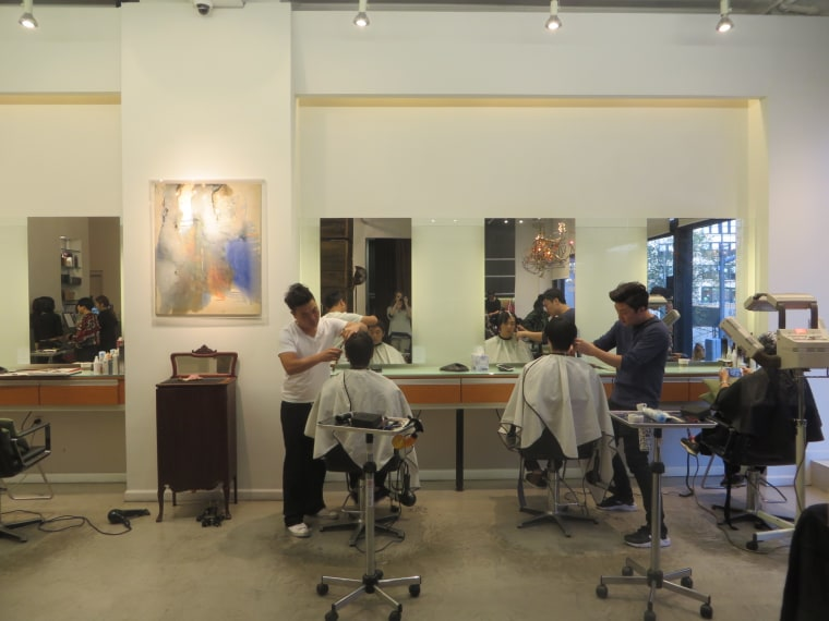 Stylists at Kakaboka in New York City work on clients as Seunghyun Suh, co-owner of the salon, greets customers.