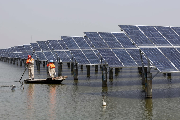 Image: Energy workers examine solar panels in China