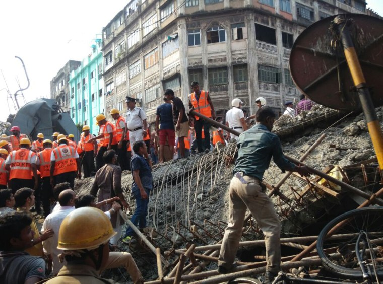Image: Locals and rescue workers clear the rubble of the partially collapsed overpass