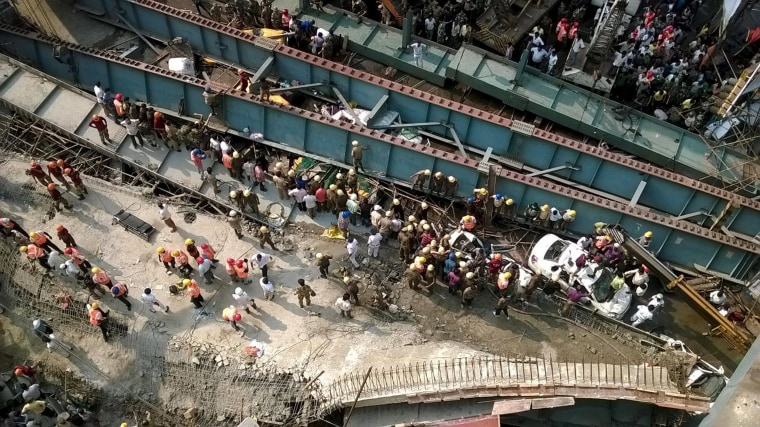 Image: People try to assist at a vehicle that is stuck in the rubble of the collapsed bridge