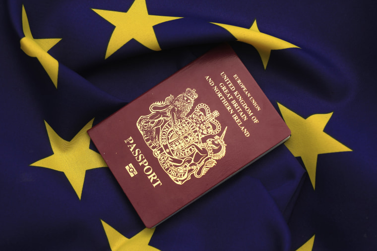 Image: United Kingdom passport sits on EU flag