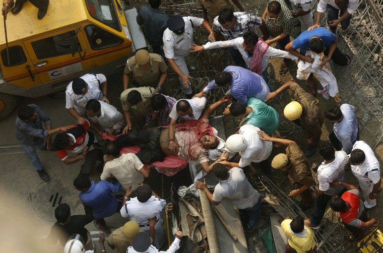 Image: Rescue members carry a victim from the site of an under-construction flyover that collapsed in Kolkata