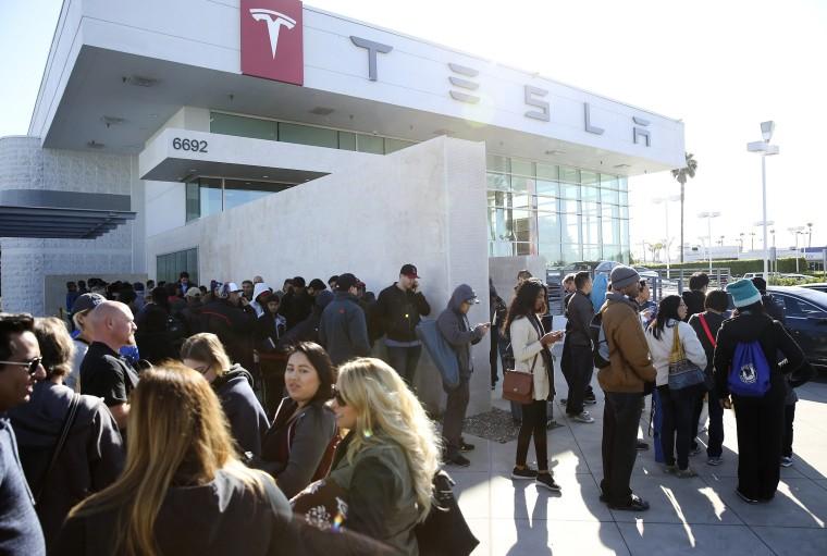 Image: Car buyers wait in line at the Tesla dealer