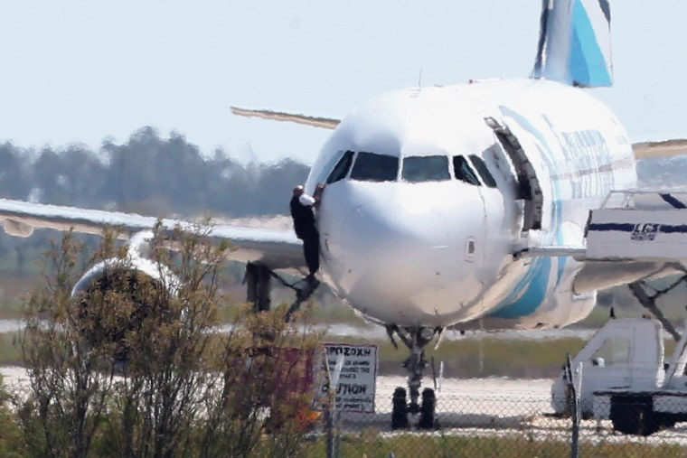 Image: A man climbs out of the hijacked EgyptAir aircraft from a pilot's window at Larnaca airport in Cyprus