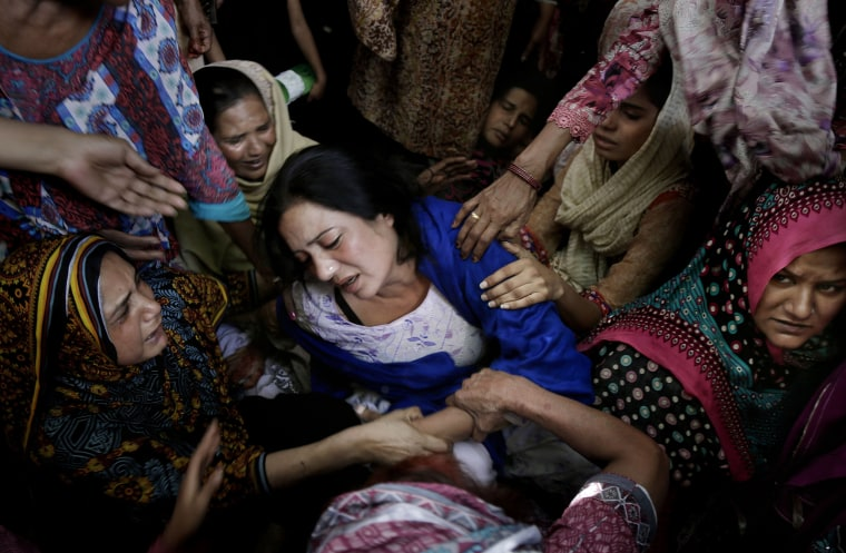 Image: Women try to comfort a mother who lost her son in bomb attack in Lahore