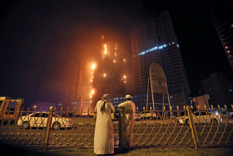 Image: Two Emirati officials watch a high-rise building as a fire spreads up the side of the building in Ajman