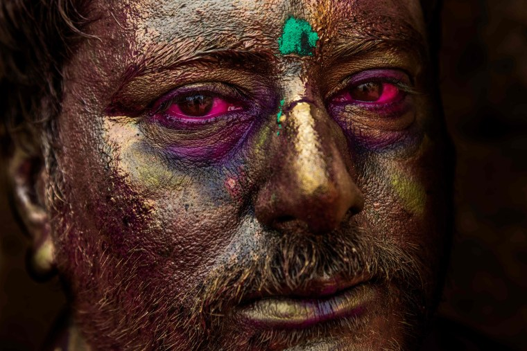 Image: A man with his face painted in gold participates in Holi