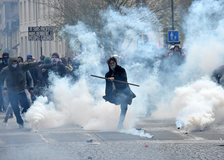Image: A protester kicks back a tear gas canister at riot police during a demonstration against the French government's labor law reforms