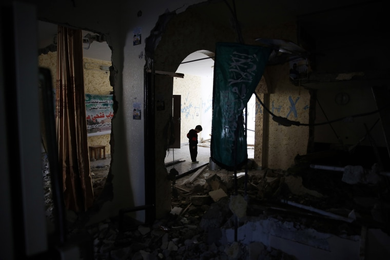 Image: A Palestinian child walks through the home of Ehab Maswada that was demolished by the Israeli army