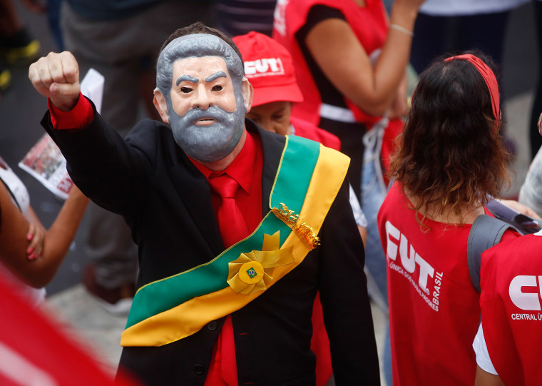 Image: A demonstrator wearing a presidential sash and a mask depicting Brazil's former President Luiz Inacio Lula da Silva attend a protest