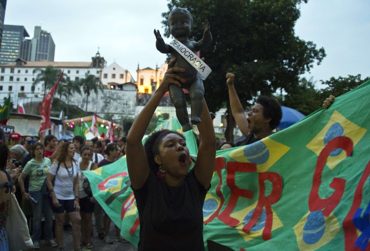 Image: A woman holds a doll in the air during a rally in Rio de Janeiro