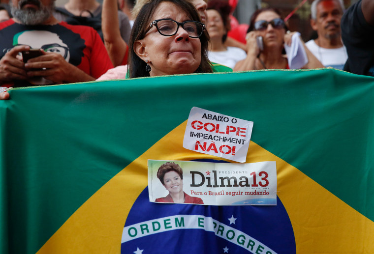 Image: A demonstrator holds a Brazilian flag with stickers in support of the president