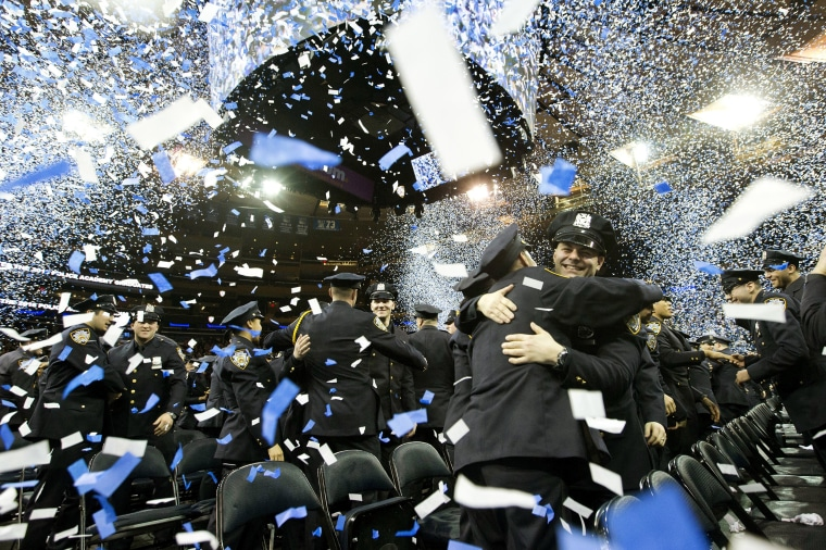Image: New police officers embrace at the end of the New York City Police Department Police Academy graduation