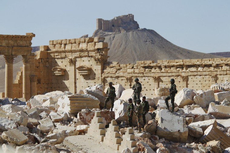 Image: Syrian army soldiers stands on the ruins of the Temple of Bel in the historic city of Palmyra