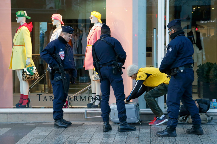 Image: French police stop a man and conduct a search on the Champs Elysees before the start of the 40th Paris Marathon