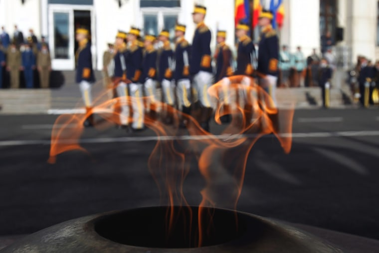 Image: Romanian soldiers are seen through the flame