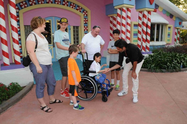 Shannon Keith Ginn's family, including his daughter, Faith, meets John Stamos on April 1, 2016, at Give Kids The World, a charity that provides vacations to families of seriously ill children.