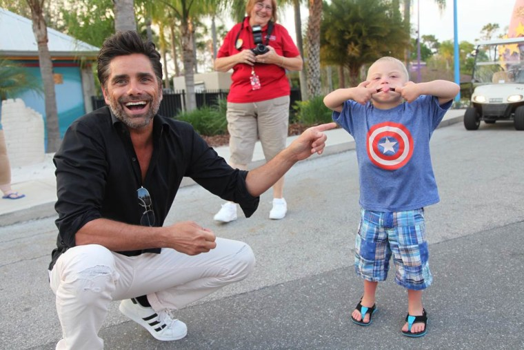 John Stamos pals around with a young guest at Give Kids The World Village.