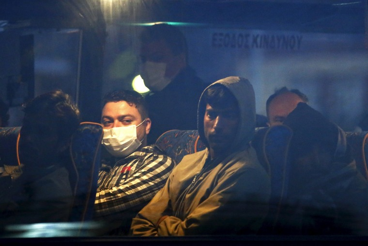 Image: Migrants on a bus before boarding a Turkish-flagged passenger boat to be returned to Turkey, on the Greek island of Lesbos