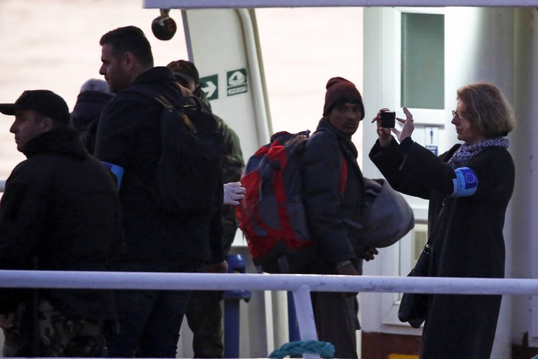 Image: A Frontex officer takes a picture as migrants board a Turkish-flagged passenger boat to be returned to Turkey