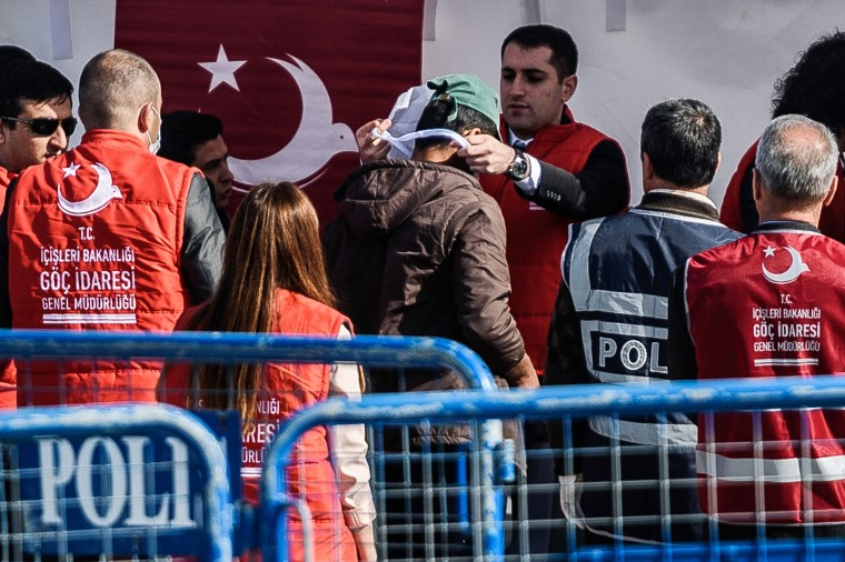 Image: A Turkish officer registers a deported migrant from Greece after arrival  at the port of Dikili district in Izmir