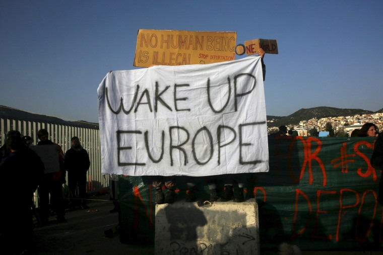 Image: Activists hold banners as they protest against the return of migrants to Turkey, at the port of Mytilene on the Greek island of Lesbos