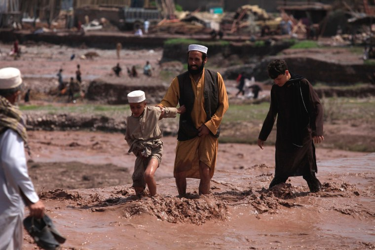 Image: Residents use a bridge covered with floodwater after heavy rain in Nowshera District on the outskirts of Peshawar