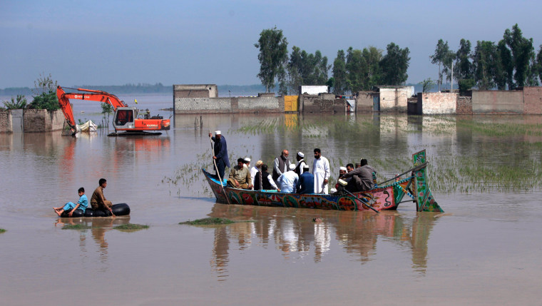 Image: Residents use boats and inner tubes to float around in floodwater after heavy rain on the outskirts of Peshawar