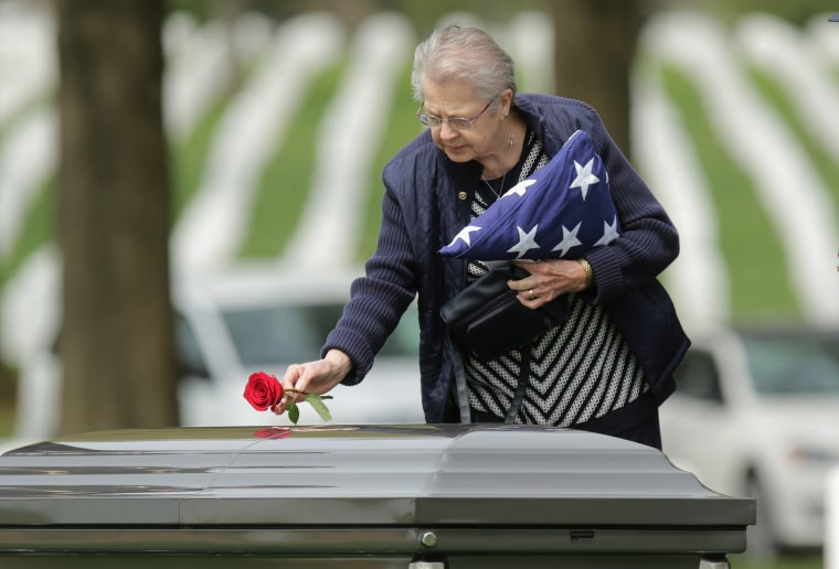 Image: Urbana Warfel, 81, places a rose on the casket of her brother, Korean War solider