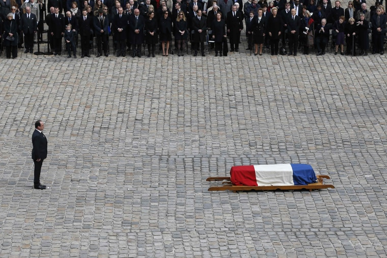Image:  Hollande stands near the flag-draped coffin of French writer and academic Alain Decaux