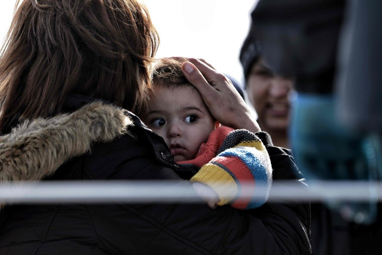 Image: A mother holds her child as migrants arrive on a Greek coast guard boat