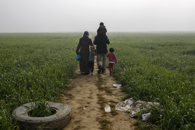 Image: A family walks through a field at a makeshift camp for migrants and refugees at the Greek-Macedonian border near the village of Idomeni