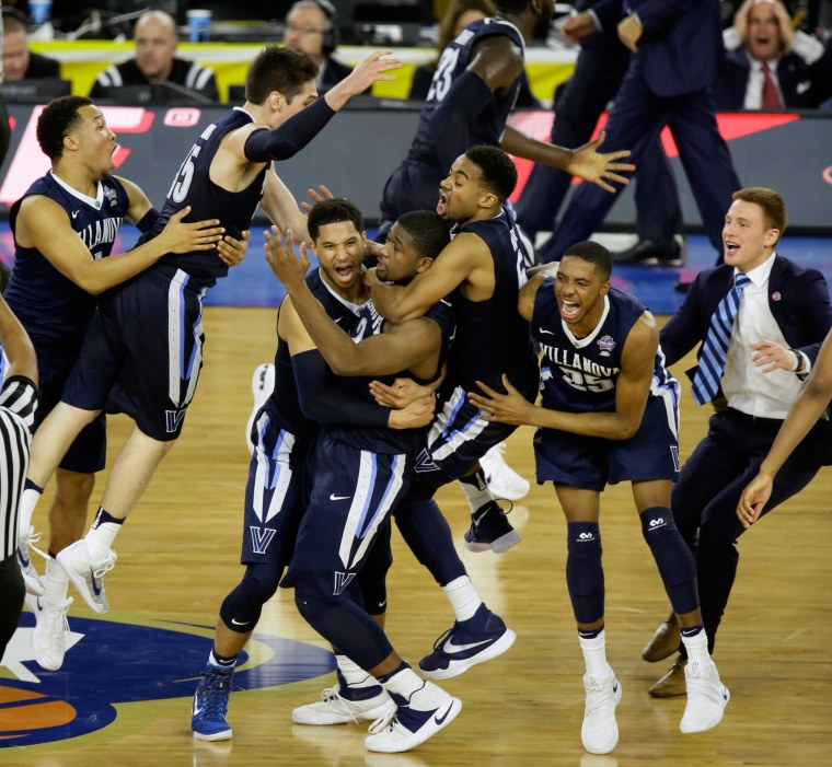 Image: Villanova players celebrate after Kris Jenkins, center, scored a game winning three point basket in the closing seconds of the game