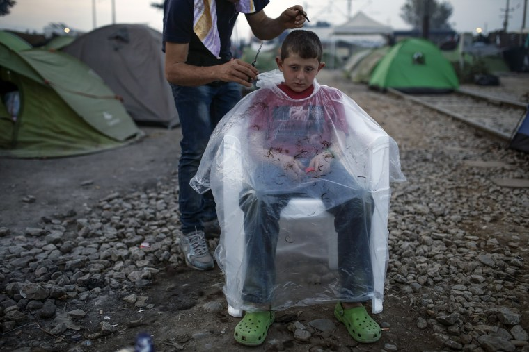 Image: A child gets a haircut at a makeshift camp for migrants and refugees at the Greek-Macedonian border near the village of Idomeni