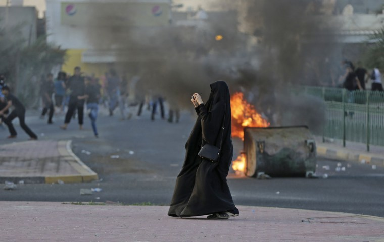 Image: A Bahraini woman photographs approaching police as anti-government protesters clashed with riot police