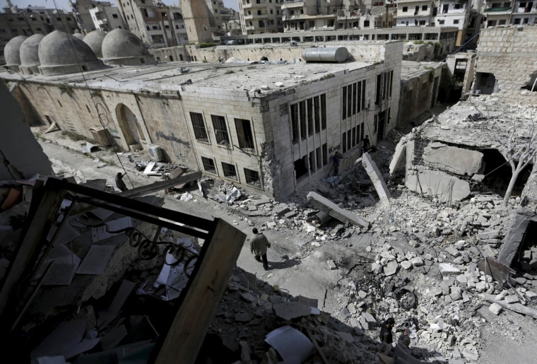 Image: People inspect the damage after a car bomb  exploded and targeted a religious center in the rebel-controlled area of Maaret al-Numan town in Idlib province
