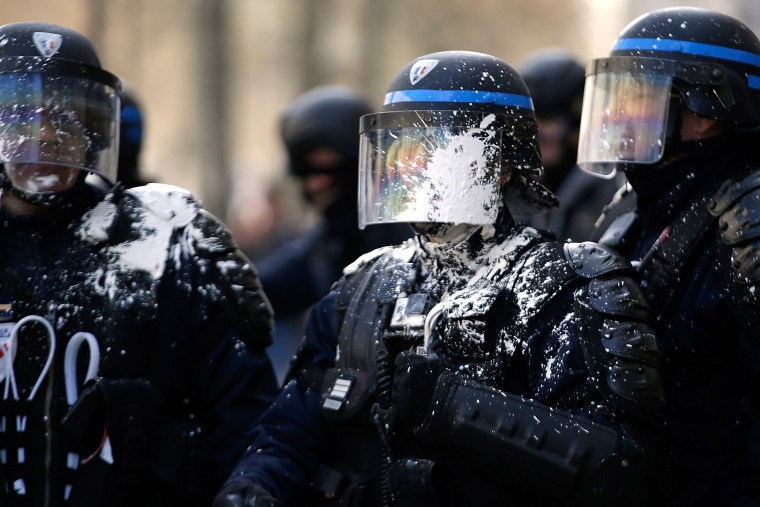 Image: Riot police are covered in paint during clashes within a demonstration of high school students