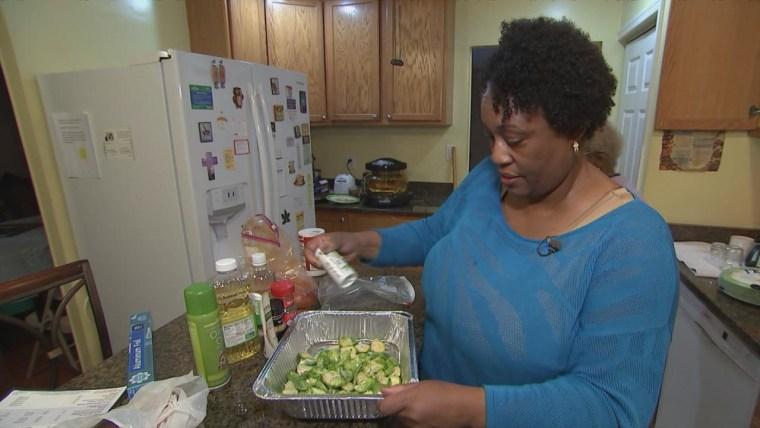 Cheryl Denby, 48, preparing food in her kitchen.