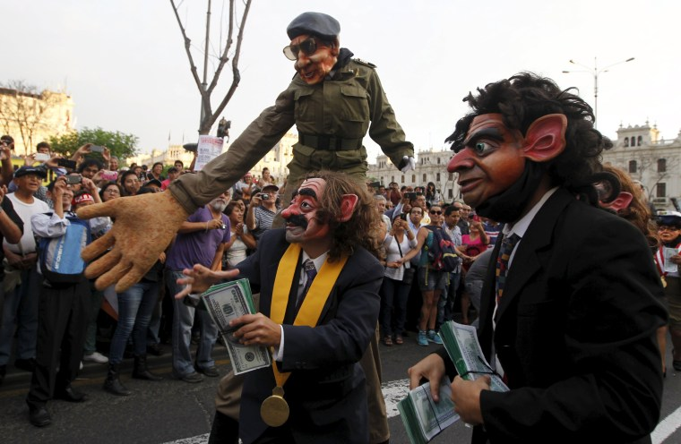 Image: Protesters representing corruption perform during a march against Peruvian presidential candidate Keiko Fujimori in downtown Lima