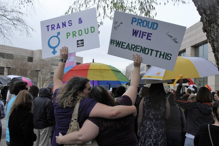 Two protesters hold up signs against passage of legislation in North Carolina, which limits the bathroom options for transgender people, during a rally in Charlotte, N.C., on March 31, 2016.