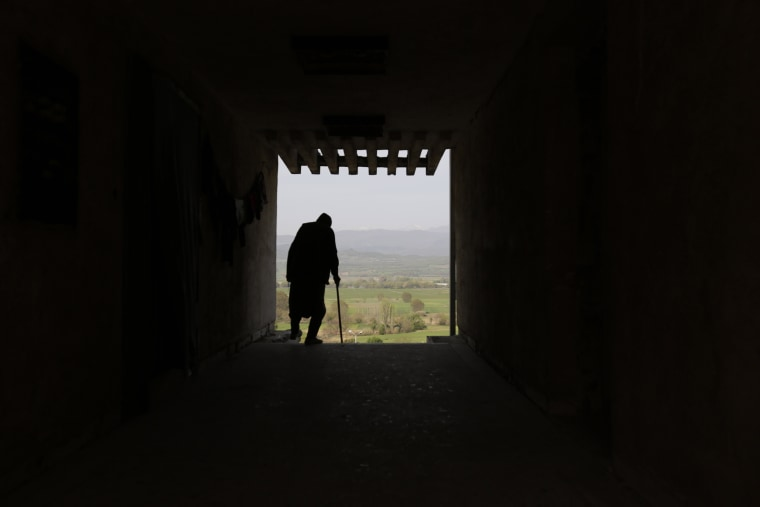 Image: An elderly migrant man stands at a doorway looking out onto the Macedonian mountains