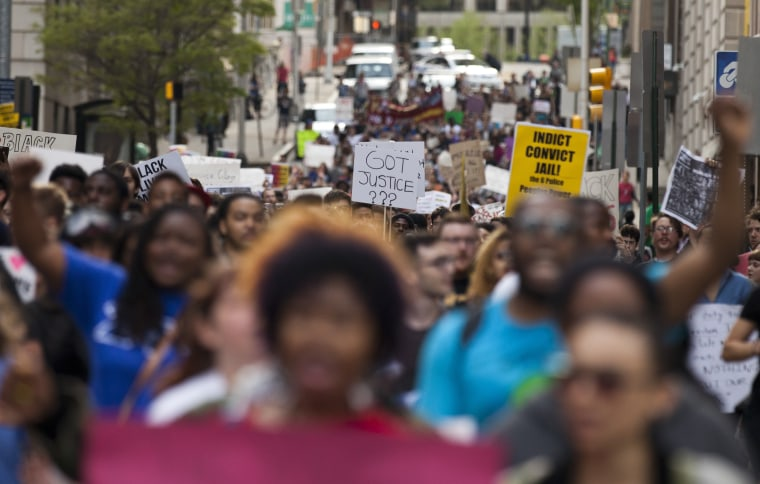 Protesters shout and carry placards during a march trough Baltimore, Maryland on April 29, 2015.  Thousands of young protesters marched through downtown Baltimore demanding justice for an African-American man who died of severe spinal injuries sustained in police custody.