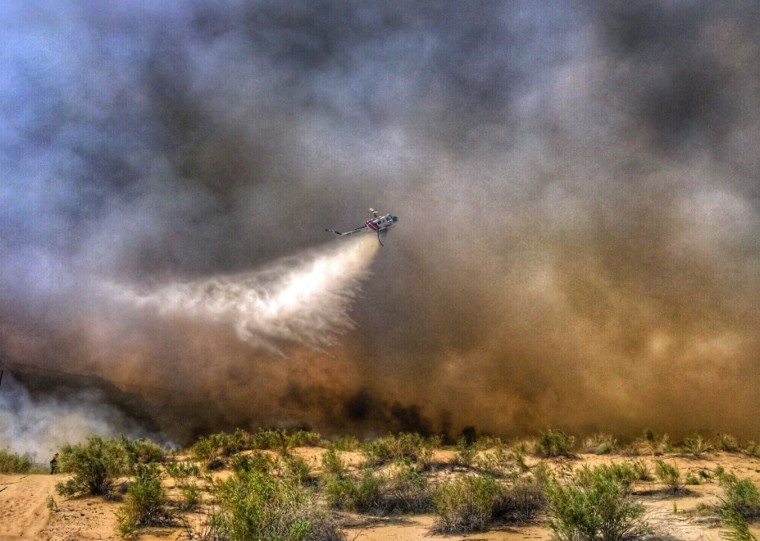 Image: A helicopter making a drop on a wildfire