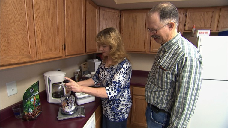 Jennifer Stewart, 54, with husband meal prepping in kitchen.