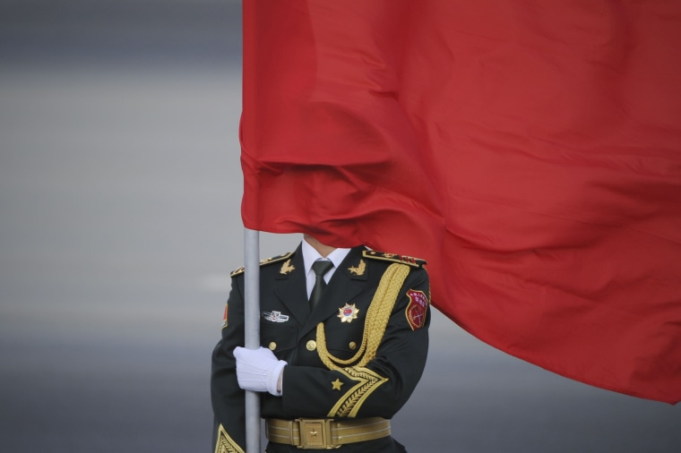 Image: A Chinese honor guard's face is covered by a red flag during a welcome ceremony outside the Great Hall
