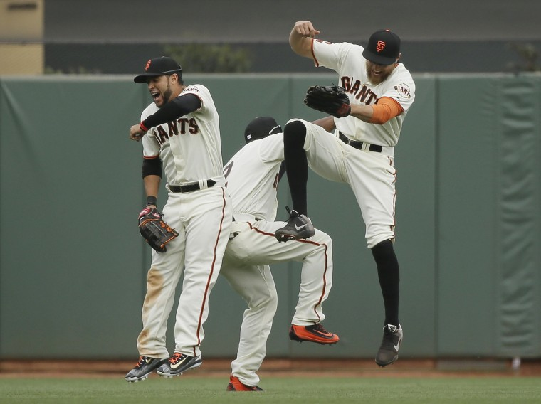 Image: San Francisco Giants outfielders celebrate at the end of their baseball game against the Los Angeles Dodgers