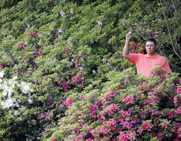 Image: Jason Dufner indicates that he found his ball in the azaleas on the 13th hole
