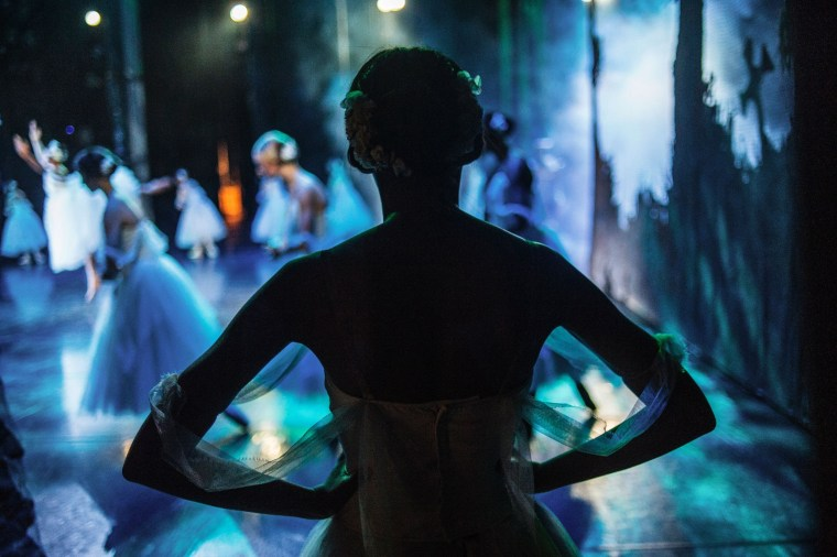 Image: A dancer waits backstage before performing during a dress rehearsal